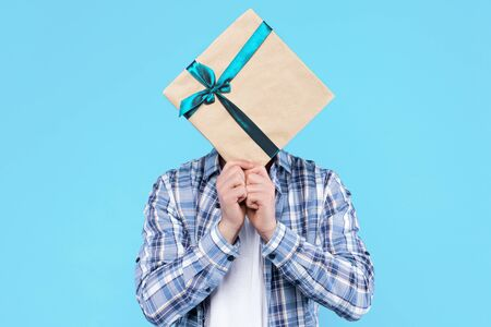 Young man in white t-shirt, checkered shirt is holding gift present box wrapped on craft paper and bow in front of face. Guy student is making surprise, standing on blue background. Holiday greeting.