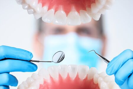 Closeup of open human jaw with teeth. Portrait of man dentist orthodontist doctor in medical mask is examining patient with dental instruments, tools in clinic. Tooth diseases, dentistry concept.