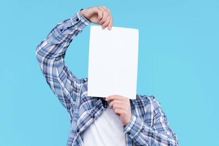 Man in white t-shirt, checkered shirt is holding blank empty paper canvas in front of face. Guy student is standing on blue background. Template for advertising, greeting, invitation card concept. Stock Photo