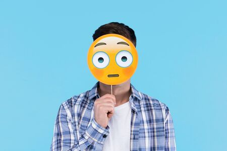 Young man in white t-shirt, checkered shirt is holding paper decorative emoticon, emoji icon, sign in front of face. Guy student is posing with photo props on blue background. Emotional portrait.
