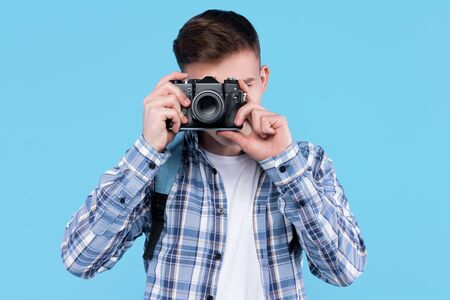 Young man photographer in white t-shirt, checkered shirt, is holding retro photo camera, standing on blue background. Guy student, traveller is making photography. Travel, trip, journey concept.
