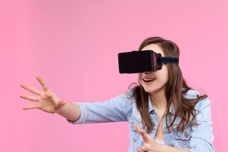 Pretty, smiling, surprised girl in VR glasses on pink background. Young woman dressed in denim jacket, white t-shirt is enjoying virtual reality world. Modern technology and devices concept.
