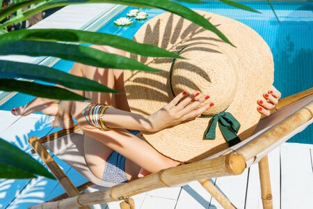 Back view of stylish woman is relaxing, sunbathing, sitting on deck chair near pool under palm. Fashionable girl in swimsuit, big hat, is resting, lounging on resort. Vacation, traveling, summer mood.