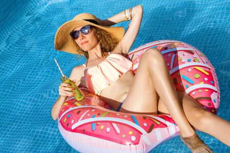 Smiling woman is relaxing, sunbathing in pool on air mattress pink donut. Fashionable girl in colorful swimsuit, hat, sunglasses is drinking fresh fruit shake, cocktail. Summer mood concept.
