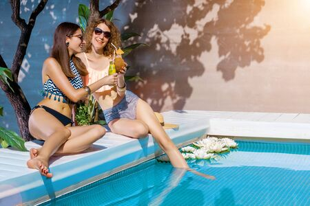 Two smiling women friends in sunglasses are relaxing, sunbathing near pool. Fashionable girls in colorful bright swimsuits are drinking fruit shakes, cocktails. Vacations, summer mood concept.