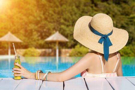 Back view of stylish woman is relaxing, sunbathing, sitting in swimming pool. Fashionable girl in swimsuit, big hat, colorful bracelets is resting, lounging on resort. Vacation, traveling, summer mood Imagens