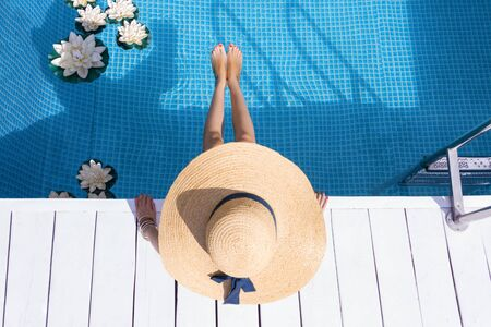 Top view female slim legs. Stylish woman is relaxing, sunbathing, sitting on edge of pool. Fashionable girl in swimsuit, big hat, is resting, lounging on resort hotel. Vacation, traveling, summer mood