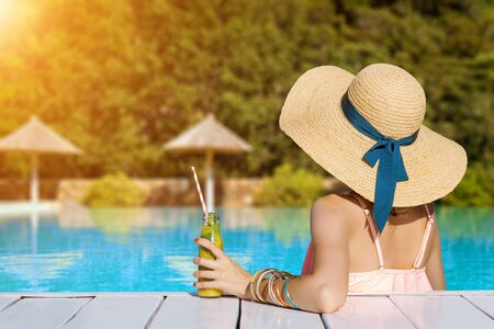 Back view of stylish woman is relaxing, sunbathing, sitting in swimming pool. Fashionable girl in swimsuit, big hat, colorful bracelets is resting, lounging on resort. Vacation, traveling, summer mood 写真素材