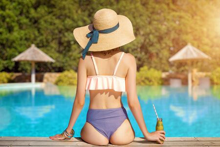 Back view of stylish woman is relaxing, sunbathing, sitting near pool. Fashionable girl in swimsuit, big hat, colorful bracelets is resting, lounging on resort. Vacation, traveling, summer mood. Imagens