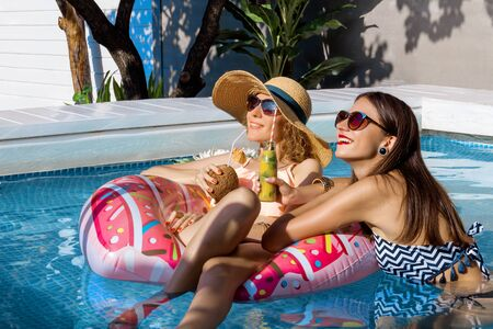 Two smiling women friends are relaxing in pool on air mattress pink donut. Fashionable girls in colorful swimsuits and accessories are drinking fruit shakes, cocktails. Summer mood concept.