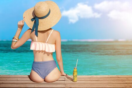 Back view of stylish woman is relaxing, sunbathing, sitting on beach near sea. Fashionable girl in swimsuit, big hat, colorful bracelets is resting, lounging on resort. Vacation, summer mood concept.