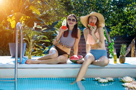 Two smiling women friends are relaxing, sunbathing near pool on beach. Fashionable girls in colorful bright swimsuits, accessories are eating watermelon, fruits. Vacations, summer mood concept.