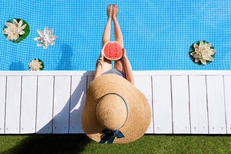 Top view female slim legs. Woman is relaxing, sunbathing, holding watermelon sitting on edge of pool. Girl in swimsuit is resting, lounging on resort hotel. Vacation, traveling, summer mood.