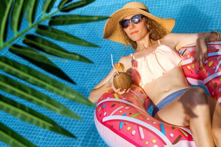 Smiling woman is relaxing, sunbathing in pool on air mattress pink donut. Fashionable girl in colorful swimsuit, hat, sunglasses is drinking coconut shake, cocktail. Summer mood concept.