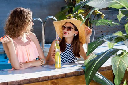 Two smiling women friends in sunglasses are relaxing, sunbathing in swimming pool. Fashionable girls in colorful bright swimsuits are drinking fruit shakes, cocktails. Vacations, summer mood concept.