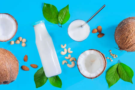 Coconut based foods are scattered on blue background. Alternative white milk in glass with straw, bottle, nuts, almonds, cashew, hazelnuts are on table. Natural healthy organic vegan vegetarian meal. Zdjęcie Seryjne