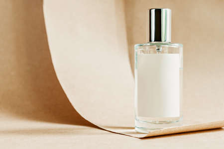Closeup glass bottle of aromatic niche floral luxury perfume on abstract background of craft paper. Cosmetics, products for personal care and concept. Minimalistic packing, branding. Foto de archivo