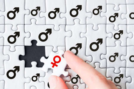 White gray puzzles with depicted male mars symbol are stacked on black background. One piece with female sign of venus located separately. Concept of gender inequality, discrimination in society. Фото со стока