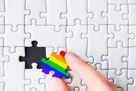 Female hand is holding piece painted in colors of rainbow. Stacked white puzzles on black background. Concept of equality, acceptance of sexual minorities lesbian, gay, bisexual, transgender.