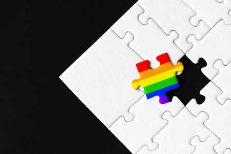One piece painted in colors of rainbow is lies separately. Background from stacked gray white puzzles. Concept of equality and acceptance of sexual minorities lesbian, gay, bisexual, and transgender. Фото со стока