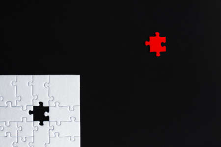 White puzzles are stacked on bottom of black background. One red piece located separately on distance. Not like everyone, outcast. Problem of gender inequality, lgbt unawareness, racism discrimination Фото со стока