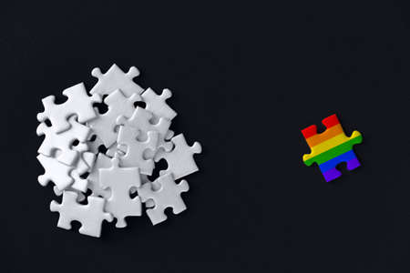 Piece painted in colors of rainbow lies separately opposite of white puzzles are scattered in bunch on black background. Concept of equality, acceptance of sexual minorities lesbian, gay, bisexual. Фото со стока