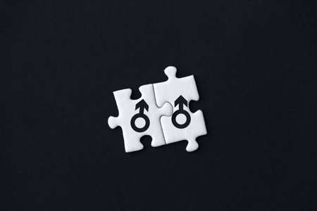 Two pieces of puzzles with printed male mars signs are stacked together on black background. Concept of equality, acceptance of sexual minorities lesbian, gay, bisexual, transgender in society.