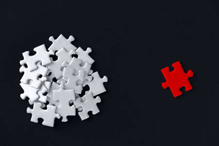 Red piece located separately opposite of white puzzles scattered in bunch on black background. Not like everyone, outcast. Problem of gender inequality, lgbt unawareness, racism discrimination.
