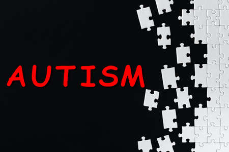 White gray pieces of puzzles are scattered, stacked on right side of black background. Red inscription on left of canvas. Problem of autism in society concept. Find solution, support, help.