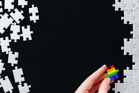 Female hand is holding piece painted in rainbow colors. Puzzles are scattered on left side and stacked on right. Becoming like everyone in society. Concept of equality, acceptance of sexual minorities