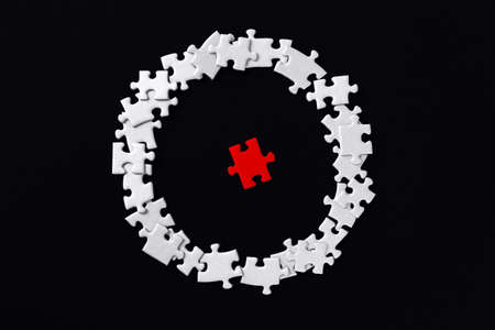 Red piece located separately in center. White puzzles are scattered around in circle on background. Not like everyone, outcast. Problem of gender inequality, lgbt unawareness, racism discrimination.