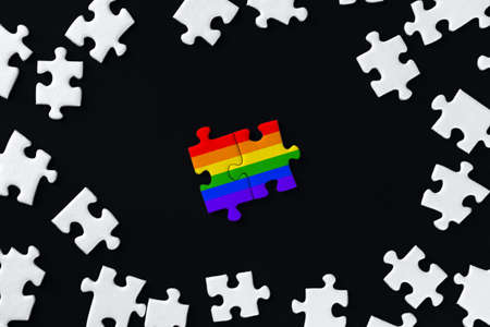 Two pieces painted in colors of rainbow lie separately in center. White puzzles are scattered around on black background. Concept of equality, acceptance of sexual minorities lesbian, gay, bisexual.