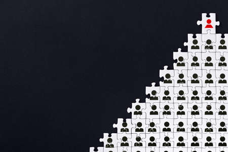 White gray puzzles with depicted male sign are stacked in pyramid on black background. One piece with female icon located on top. Concept of gender inequality, discrimination in society, at work.