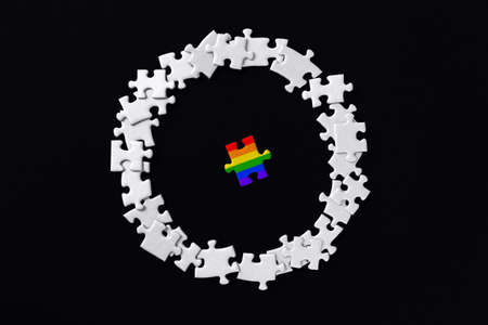Piece painted in colors of rainbow lies separately. Puzzles are scattered around in circle on background. Concept of equality, acceptance of sexual minorities lesbian, gay, bisexual, transgender. Фото со стока