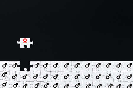 White gray puzzles with depicted male mars symbol are stacked on bottom of black background. One piece with female sign of venus located separately on distance. Concept of gender inequality in society