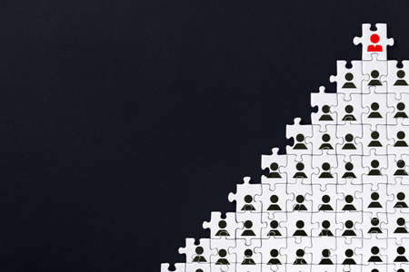 White gray puzzles with depicted female sign are stacked in pyramid on black background. One piece with male icon located on top. Concept of gender inequality, discrimination in society, at work. Фото со стока