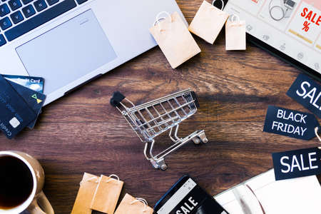 Laptop, credit cards, smartphone, cart, cup of coffee, tablet are on table. Preparation for online shopping. Ready to buy goods. Black friday concept. Discount seasonal sale. Cashless payment.