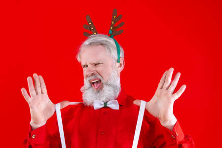 Happy, old man with long white beard and mustache posing, smiling, showing his suspenders  Positive modern male in horns of Rudolph wearing stylish red shirt.  Winter holidays celebration concept. Stock Photo