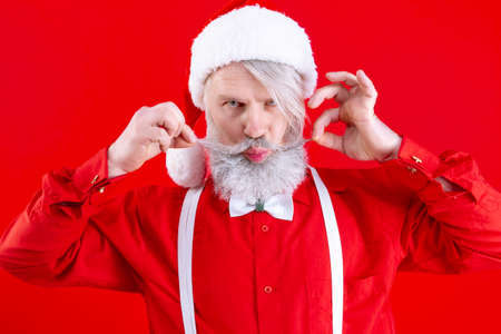 Positive modern Santa Claus, wearing stylish red hat, shirt and white suspenders. Happy, old man with long white beard holding his mustache and grimace. Winter holidays, new year celebration concept.