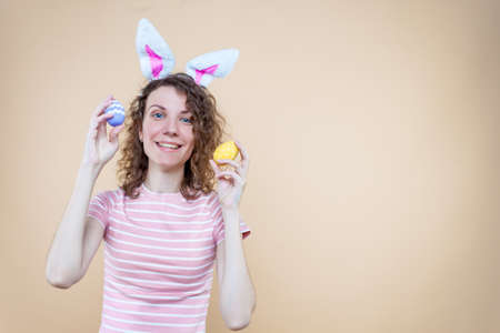Pretty smiling girl in bunny ears, striped pink t-shirt is holding eggs. Young curly woman is preparing for celebration. Happy easter, spring concept. Carnival, seasonal party decor for holiday.