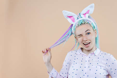 Pretty cute girl in bunny ears, pink shirt is winking. Young woman with colored dreadlocks is preparing for celebration. Happy easter, spring concept. Carnival, seasonal party decor for holiday.