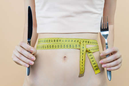 Closeup of female slender tummy tied with centimeter tape. Young woman is holding fork, knife. Diet nutrition, weight loss concept. Healthy lifestyle. Disease of anorexia, bulimia.