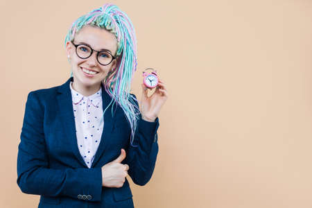 Successful business lady is smiling, holding pink alarm clock. Young woman with colored dreadlocks, in glasses, jacket, completed job tasks on term. Time management, deadline concept.