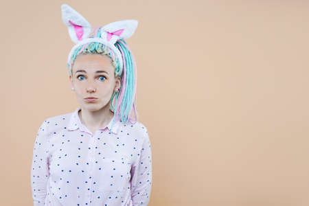Young woman with fashion blue hair wearing easter rabbit ears over pink background cheerful with a smile of face pointing with hand and finger up to the side with happy and natural expression on face Imagens