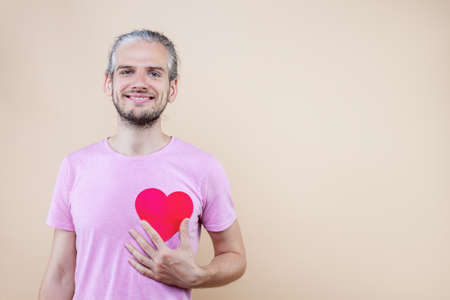 Cute smiling boy is holding red decorative sign of heart. Young man cupid in pink t-shirt is expressing sympathy, feelings. Happy St. Valentine's Day. Fall in love. Like concept. Imagens