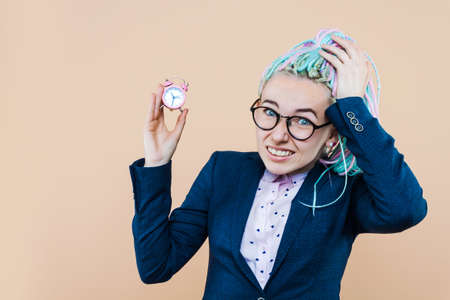 Business lady is holding pink alarm clock on beige background. Young woman with colored dreadlocks, in glasses, jacket, in shock because she is late. Stress, deadline concept.