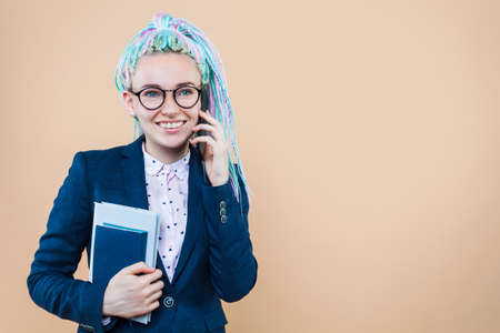 Business lady with colored dreadlocks is talking on phone, holding planner book. Woman girl in suit is solving working issues managing tasks remotely. Entrepreneur, director, head of company concept. Imagens