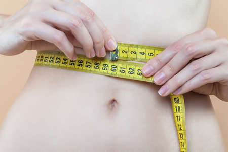Closeup of female slender tummy tied with yellow centimeter tape. Young woman is measuring parameters of figure. Diet nutrition, weight loss concept. Healthy, sports lifestyle. Disease of anorexia.