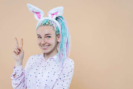 Pretty cute girl in bunny ears, pink shirt is smiling. Young woman with colored dreadlocks is preparing for celebration. Happy easter, spring concept. Carnival, seasonal party decor for holiday.