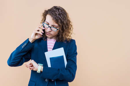 Serious business lady is holding smartphone, documents, note book. Young woman in suit is solving working issues. Leader is managing tasks remotely. Entrepreneur, director, head of company.